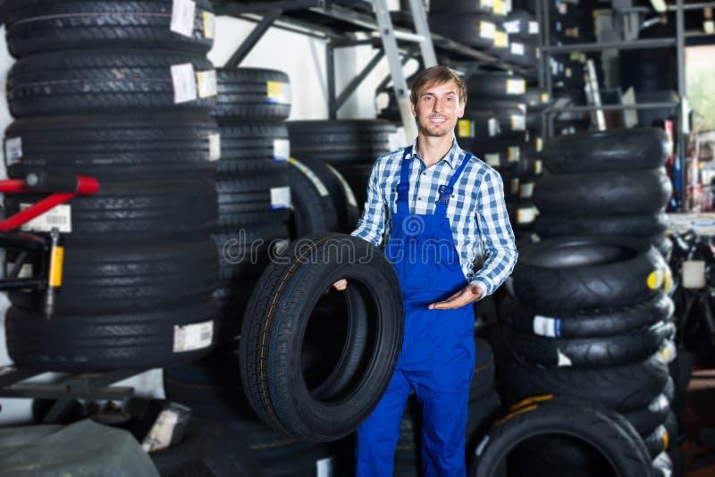 年轻友好的技工人与车胎一起使用在车间 免版税库存图片