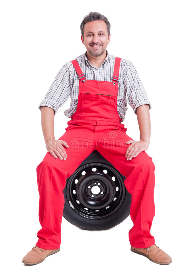 友好的技工坐车轮轮胎 免版税库存图片