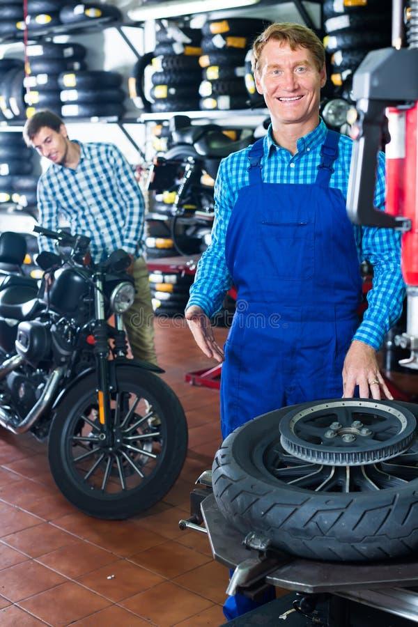友好的技术员人与摩托车的轮子一起使用 免版税图库摄影