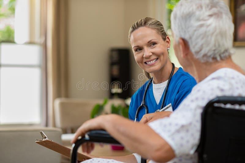 友好的护士谈话与资深患者 免版税库存照片