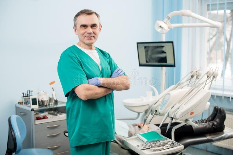 友好的男性牙医用牙科设备在牙齿办公室 免版税库存图片