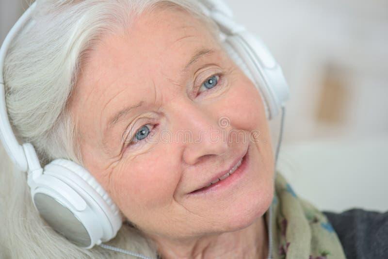 友好的老妇人听的音乐 免版税库存图片