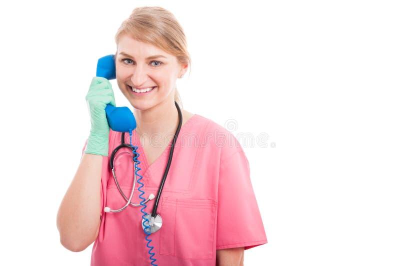 友好的医疗护士夫人微笑的讲话在电话 图库摄影
