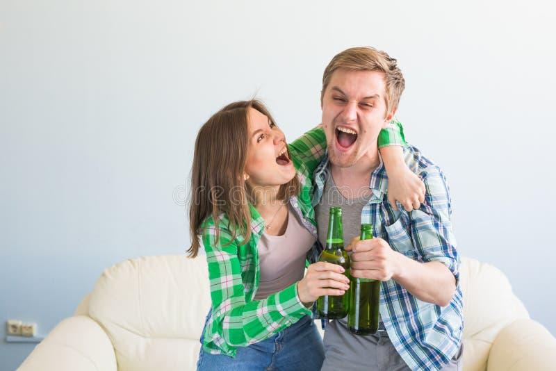 友谊、体育、娱乐和足球世界杯-有芯片和啤酒观看的体育的愉快的朋友在家 库存图片