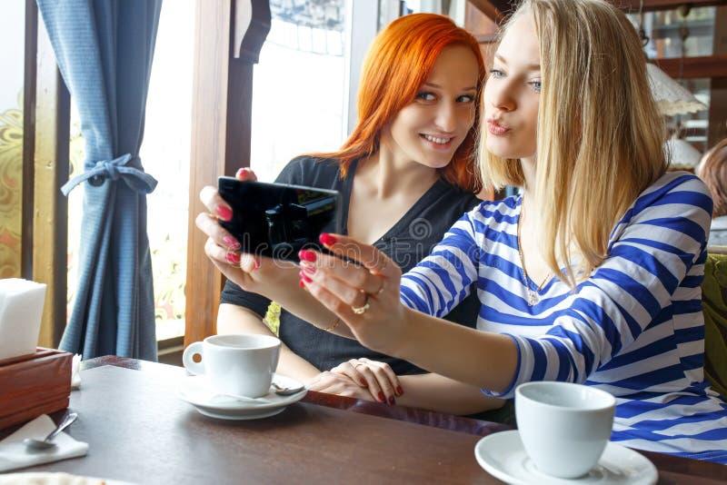 友谊和技术 使用智能手机的两个俏丽的女孩,当喝茶在咖啡馆时 库存图片