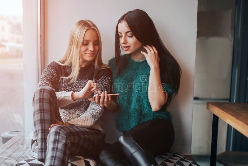 友谊和技术 使用智能手机的两个俏丽的女孩,当喝茶或咖啡在咖啡馆时 免版税库存照片