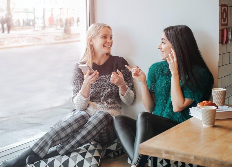 友谊和技术 使用智能手机的两个俏丽的女孩,当喝茶或咖啡在咖啡馆时 免版税库存图片