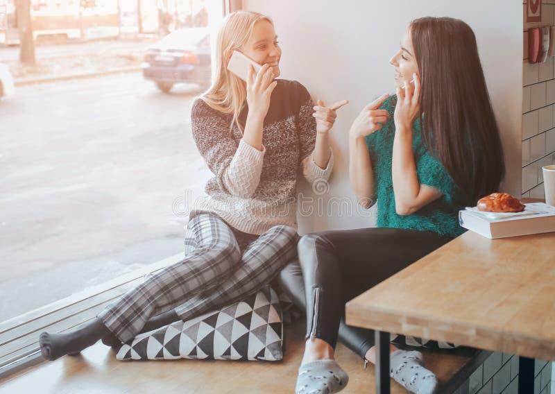 友谊和技术 使用智能手机的两个俏丽的女孩,当喝茶或咖啡在咖啡馆时 库存图片