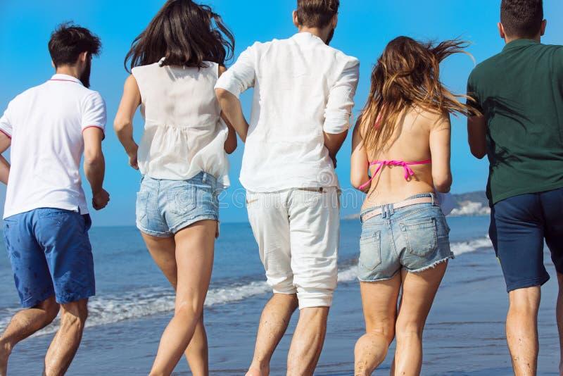 友谊自由海滩暑假概念-青年人跑 免版税库存照片