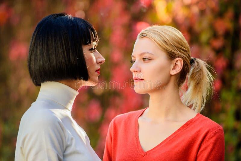 友谊问题竞争和嫉妒 俏丽的女朋友姐妹 目光接触 看彼此的妇女与 免版税库存图片