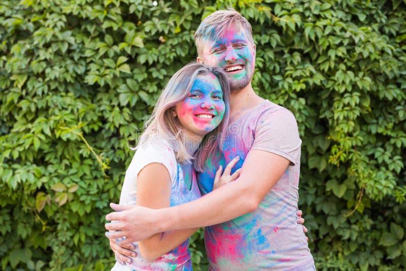 友谊,holi,人概念-使用与颜色的年轻夫妇节日在holi节日  免版税库存图片