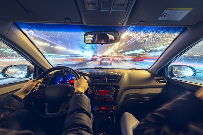 双人在汽车移动以最快速度在晚上 图库摄影