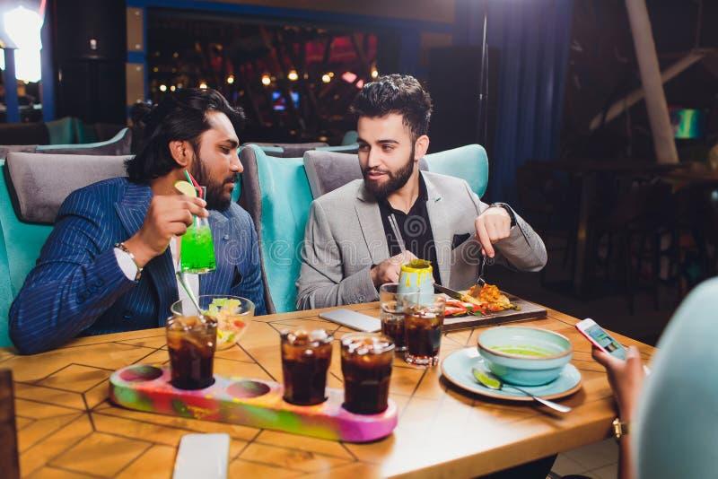 双人在酒吧举行玻璃坐在逆,饮用的鸡尾酒,遇见酒吧的快乐的朋友传达谈话 免版税库存图片