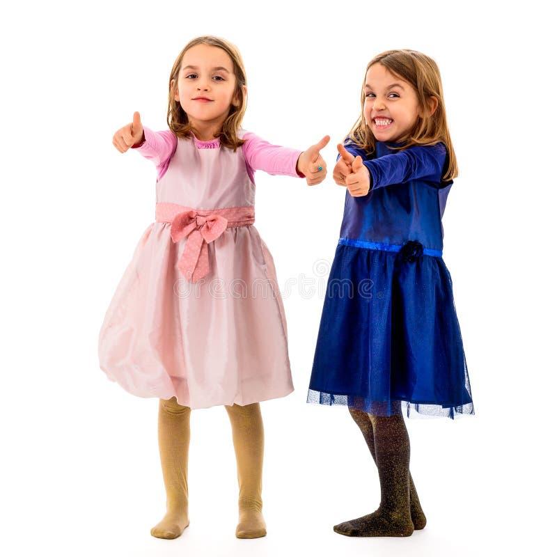 双女孩显示赞许标志或姿态 免版税库存照片