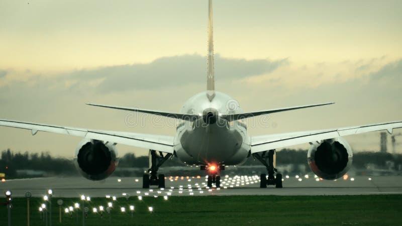 双开始从机场的引擎商业飞机起飞在晚上,背面图 免版税图库摄影