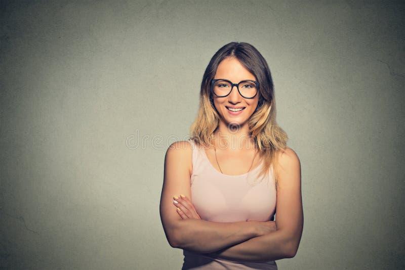 戴双臂被交叉的和眼镜的愉快的妇女 库存照片