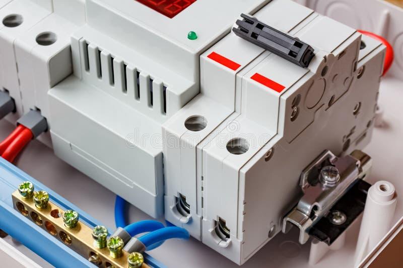 双重在白色塑料登上的箱子的输入自动开关和电压防幅器特写镜头 免版税库存照片