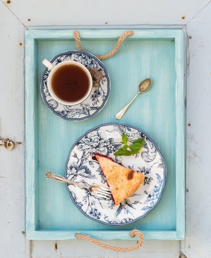双重外壳李子饼和红茶片断在葡萄酒瓷杯子,蓝色木盘子 顶视图 免版税图库摄影
