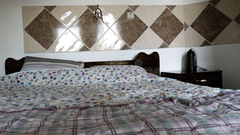 双重大床在一间屋子里在一个熟悉的家 有灯的床边蚊子的 菱形瓦片和梦想俘获器在头  免版税库存照片