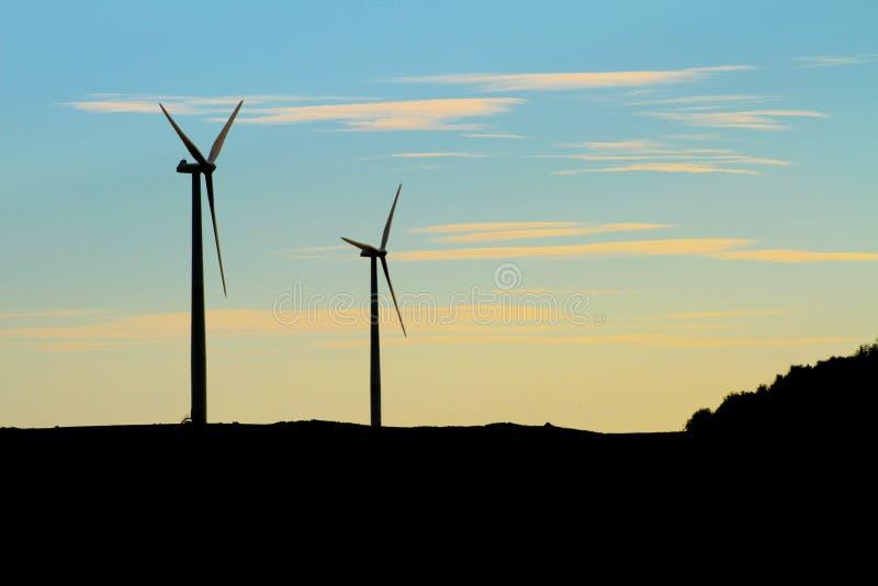 双风轮机剪影在黎明 免版税库存照片