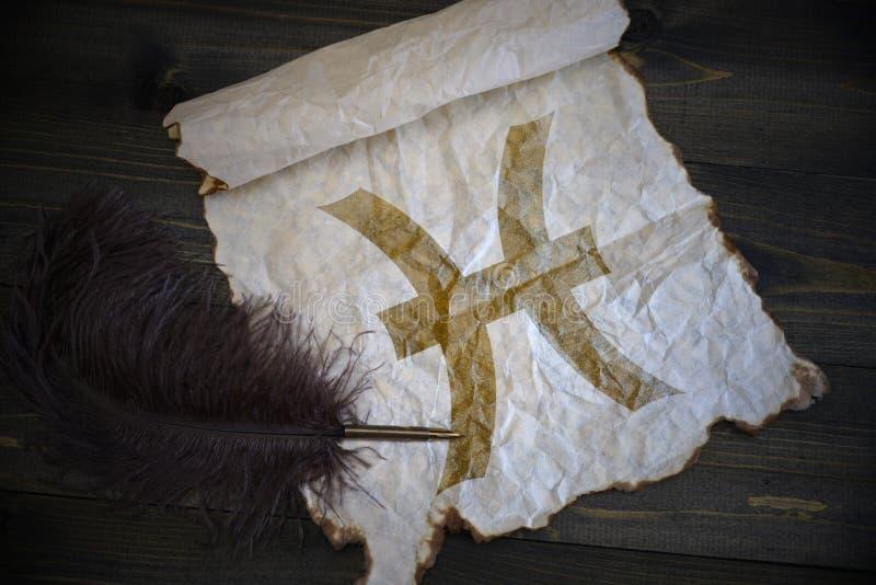 双鱼座黄道十二宫在葡萄酒纸的与在木书桌上的老笔 库存照片