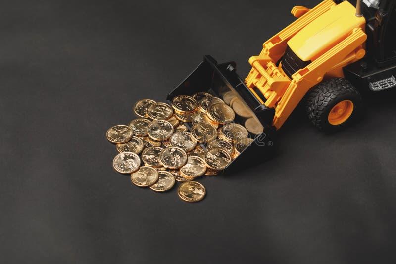 反向铲金钱硬币的拖拉机犁耙 库存照片