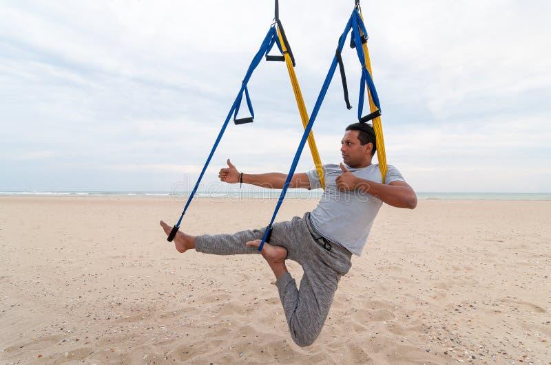 反地心引力的瑜伽,做瑜伽锻炼或飞行瑜伽在海背景的人 库存照片