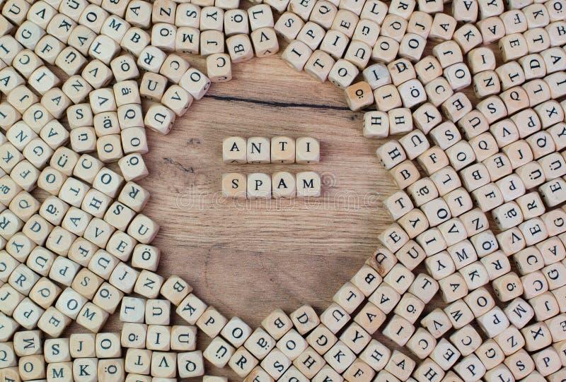 反垃圾短信,反垃圾短信的德国文本,在信件的词在立方体在桌上切成小方块 免版税图库摄影