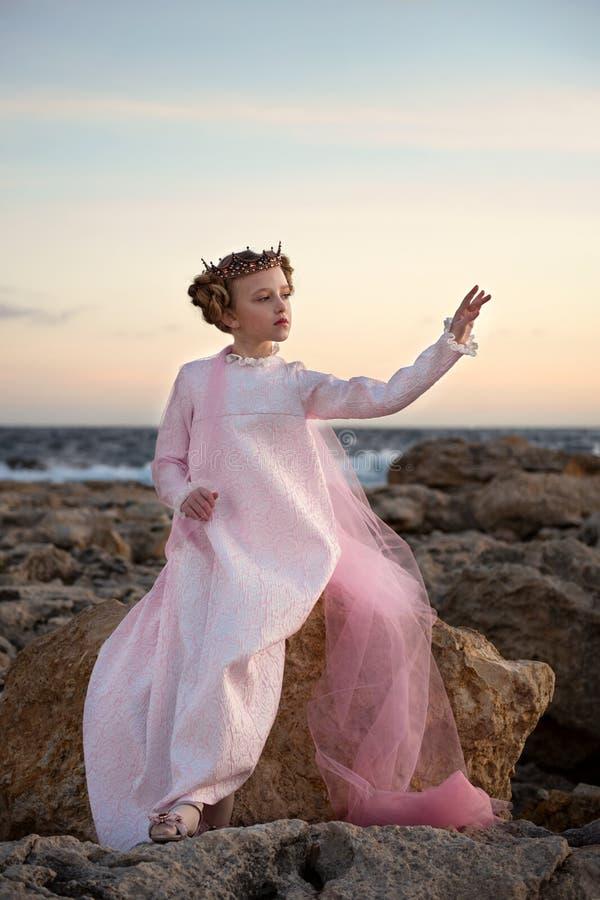 反复无常的不安定的公主女孩坐石头由一件桃红色礼服的海有面纱和冠的 免版税库存图片