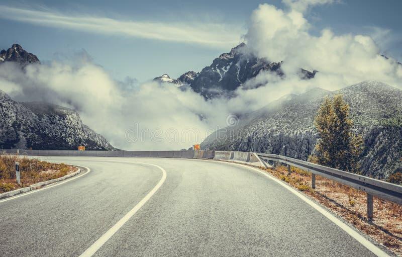 反对一个壮观的山风景的背景的汽车高速公路 库存图片