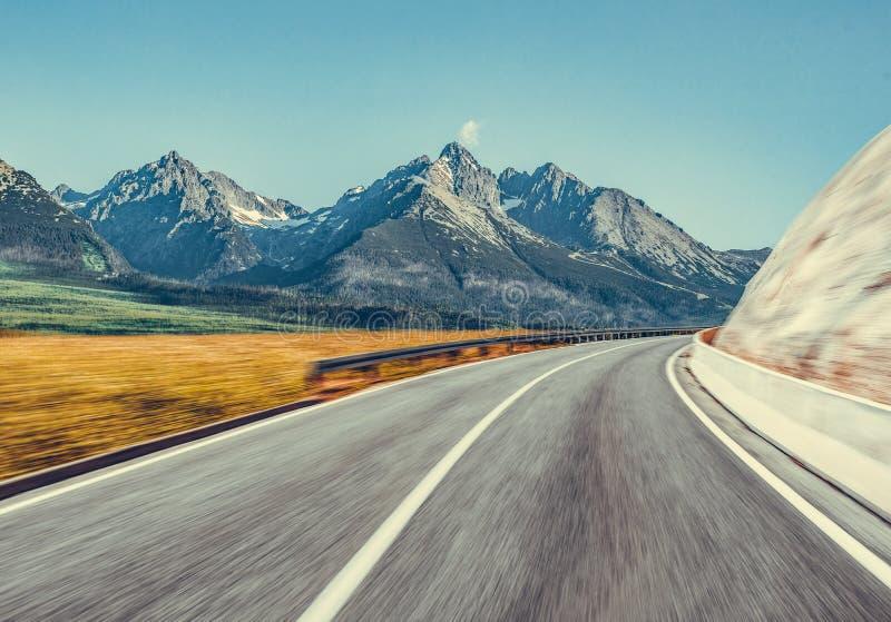 反对一个壮观的山风景的背景的汽车高速公路 免版税库存照片