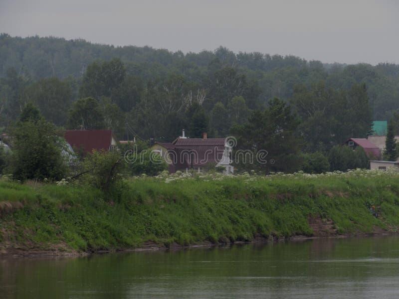 反对一个有薄雾的风景的背景的小轻的乡间别墅与河和林木的在距离 库存图片