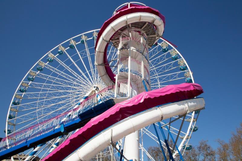 反对一个清楚的天空蔚蓝重要人物转盘的五颜六色的弗累斯大转轮有白色桃红色巨型幻灯片的 库存照片