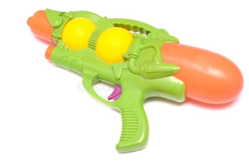 反对一个白色背景的绿色玩具水枪 免版税库存图片