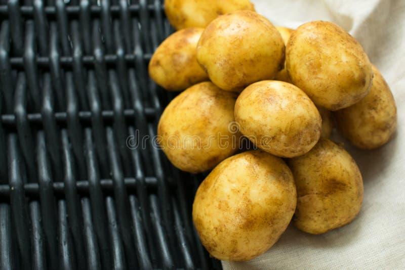 反对一块黑篮子和餐巾的土豆 免版税图库摄影