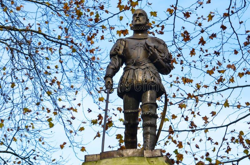 反对与凋枯的黑暗叶子的秋天树之前围拢的清楚的蓝天的雕塑 免版税库存照片