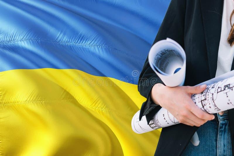 反对乌克兰挥动的旗子背景的乌克兰建筑师妇女藏品图纸 建筑和建筑学概念 免版税图库摄影