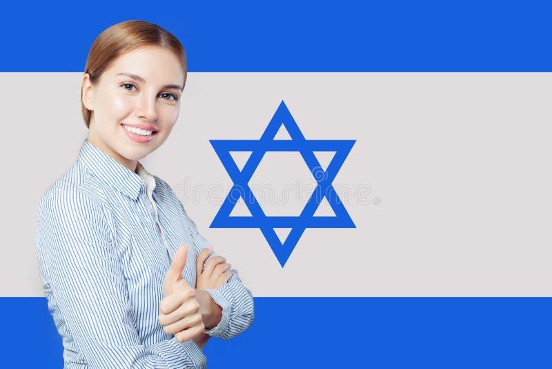 反对以色列旗子背景的逗人喜爱的愉快的年轻女人 免版税库存图片