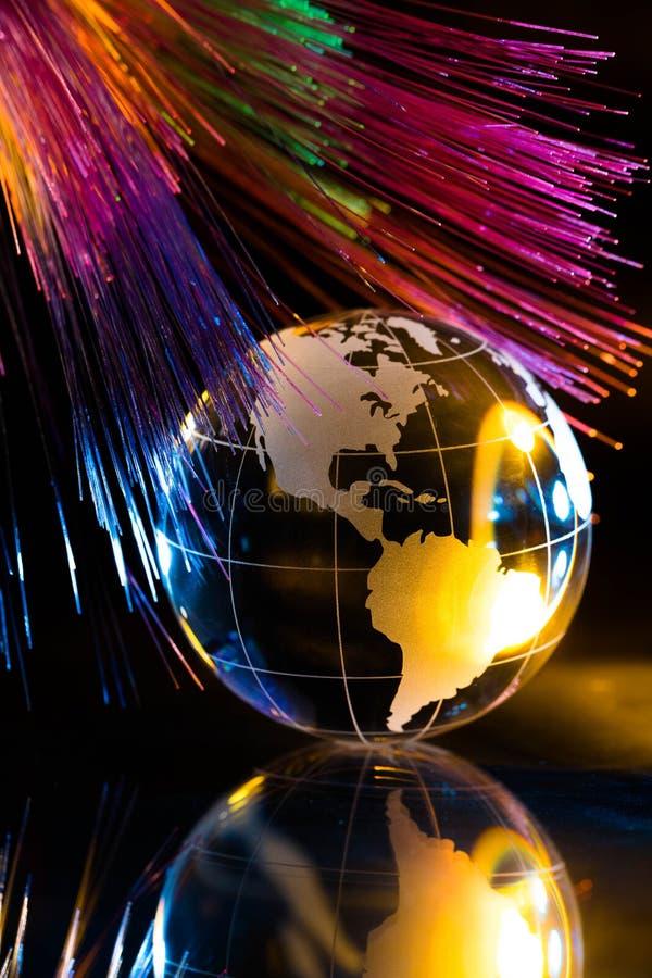 反对光纤背景的玻璃地球 免版税库存图片