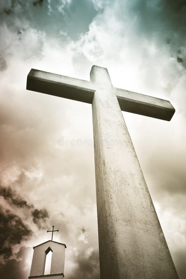 反对剧烈的多云天空的具体基督徒十字架-概念图象 免版税库存照片