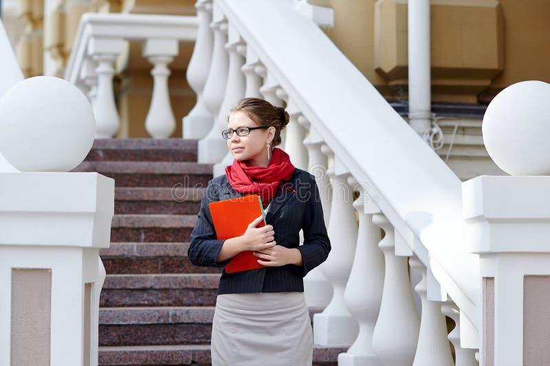 年轻反对办公楼的女商人举行手中文件夹在楼梯附近的街道上 图库摄影