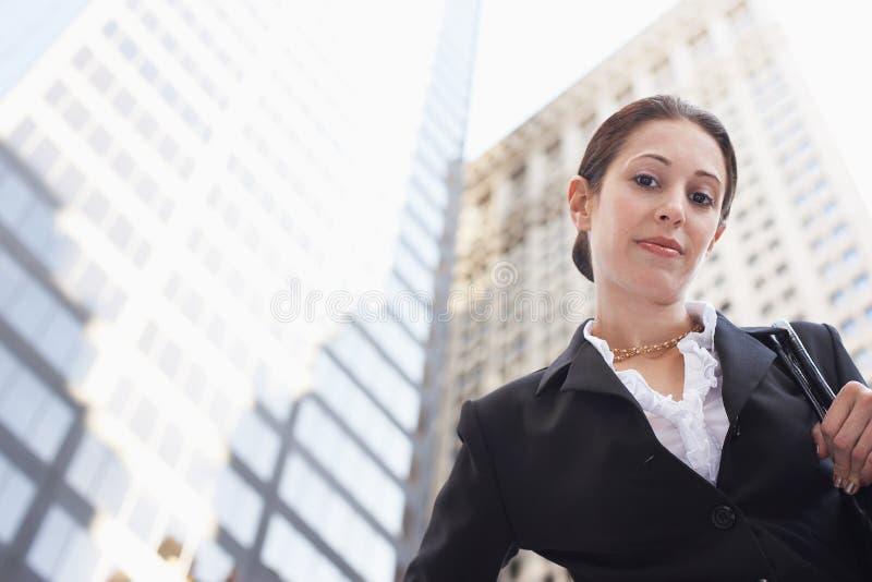 反对办公楼的确信的女实业家 免版税库存图片