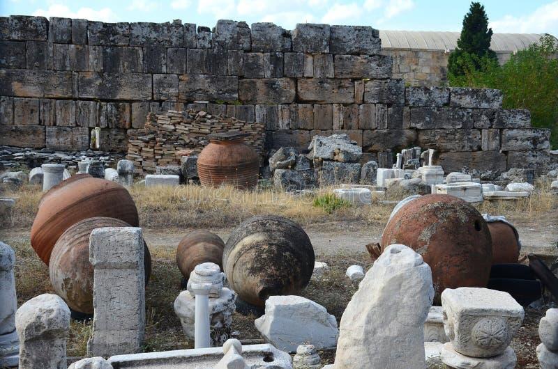 反对古城希拉波利斯的废墟的背景的巨大的古色古香的黏土油罐在棉花堡附近的 免版税库存照片