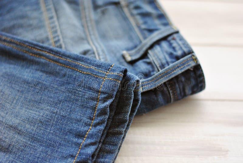 反对土气白色木背景的蓝色牛仔布牛仔裤裤子 库存图片