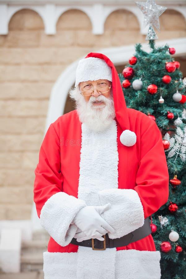 反对圣诞树的圣诞老人 免版税库存照片