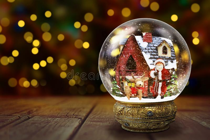 反对圣诞灯背景的雪地球 免版税库存图片