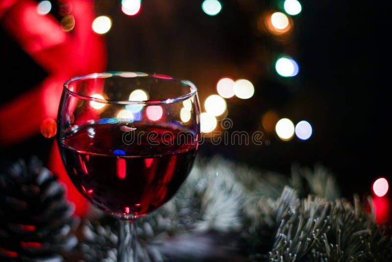 反对圣诞灯装饰背景,圣诞节的前夕的两块红葡萄酒玻璃 免版税图库摄影