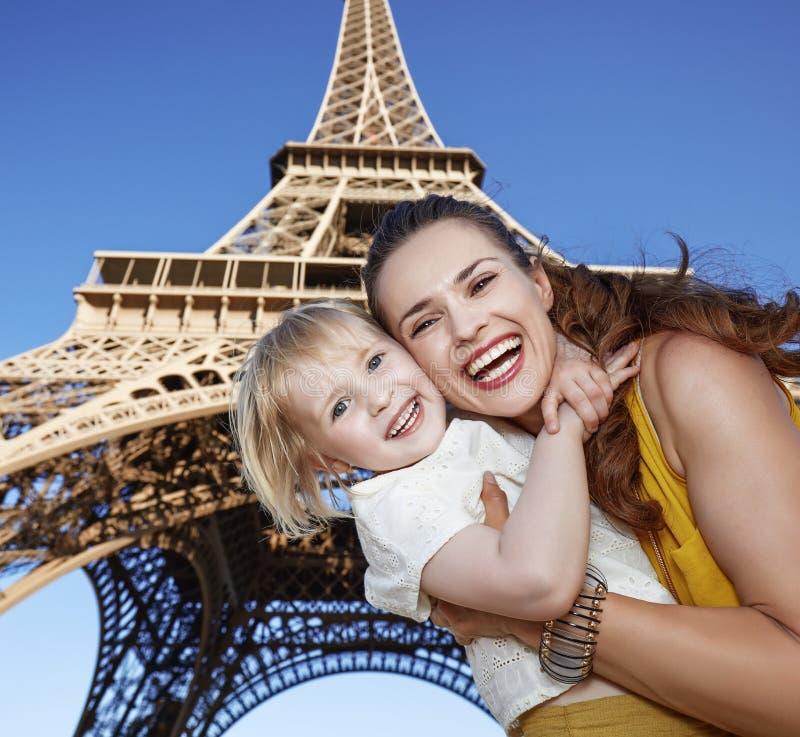 反对埃佛尔铁塔的微笑的母亲和儿童游人在巴黎 免版税图库摄影