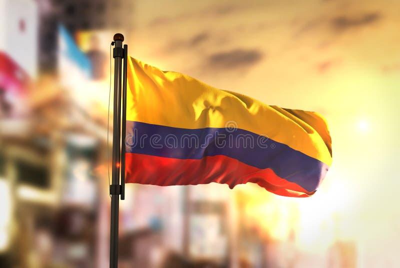 反对城市被弄脏的背景的哥伦比亚旗子在日出Backlig 免版税库存照片
