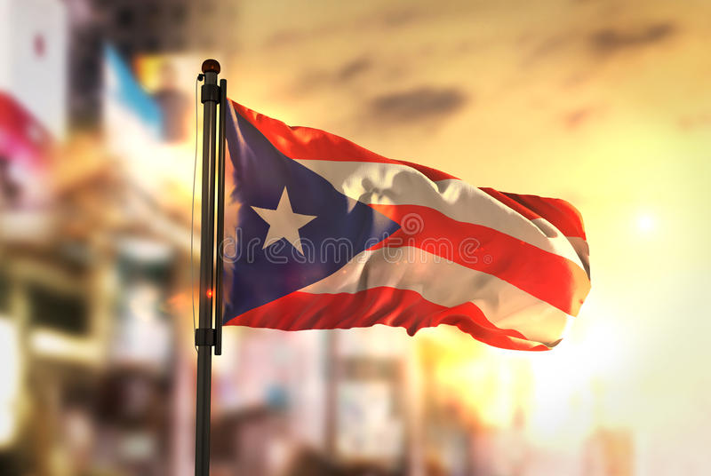反对城市被弄脏的背景的波多黎各旗子在日出后面 图库摄影